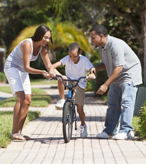 boy riding bike with parents helping