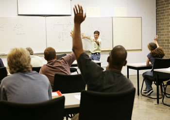 Adult learning classroom with teacher calling on student with hand raised